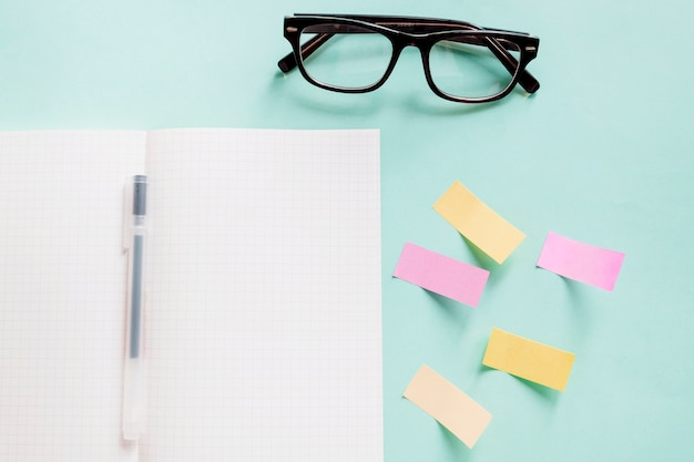 Open notebook with pen near adhesive notes and spectacles on colorful background Free Photo