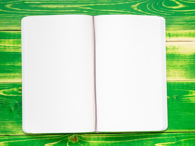 Open notebook with two, white pages, lying on a bright green wooden table, mock-up Premium Photo