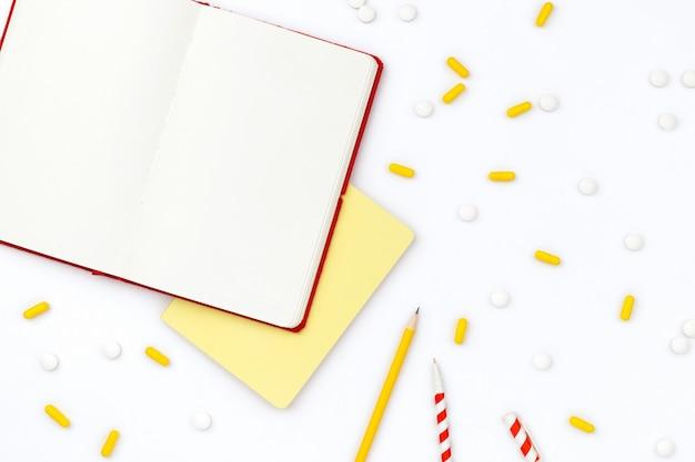 열린 메모장 및 흰색 테이블에 흩어져있는 약 프리미엄 사진