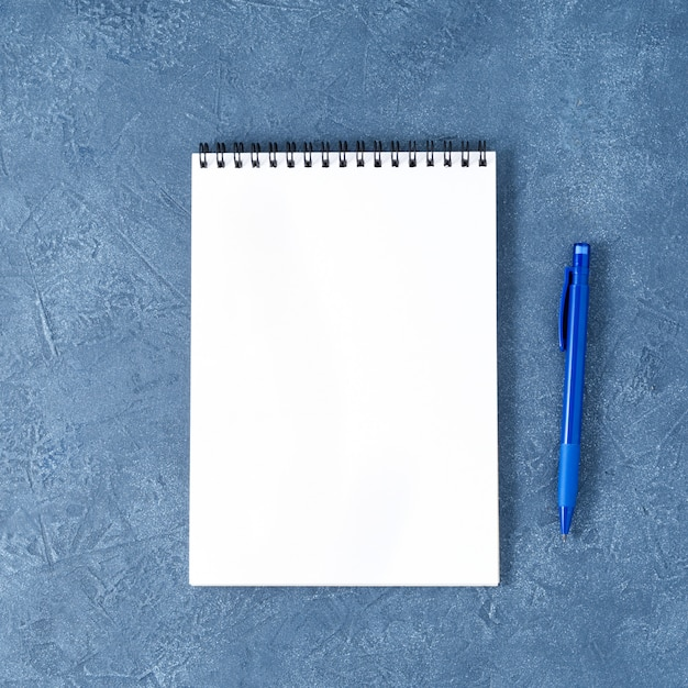 The open notepad  clean white page on aged dark blue stone table, top view Premium Photo