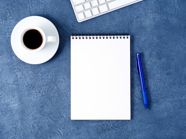 The open notepad  clean white page, pen and coffee cup on aged dark blue stone table, top view Premium Photo