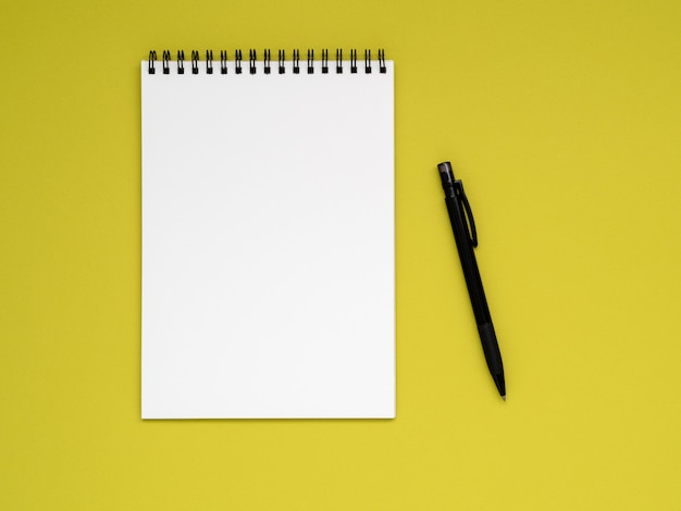 Open notepad on the spiral with a clean white page and pencil on a bright yellow background color Premium Photo