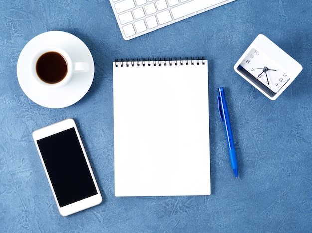 The open notepad with clean white page, coffee cup on blue table, top view. Premium Photo