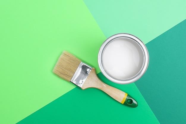 Open paint enamel cans on green palette samples Premium Photo