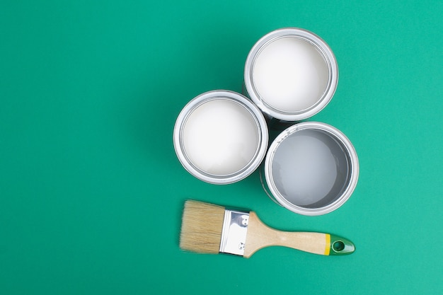 Open paint enamel cans on green turquoise palette samples Premium Photo