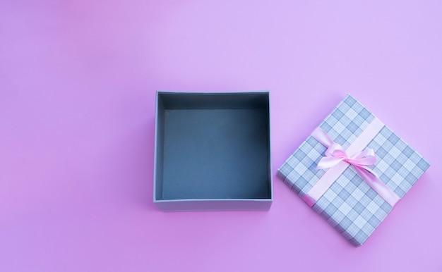 Открытая подарочная коробка с розовым бантом на розовом фоне Premium Фотографии