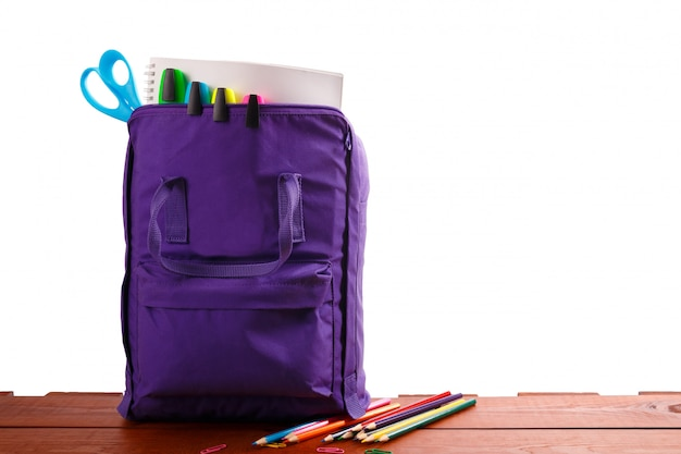Open purple backpack with school supplies on wooden table. back to school Premium Photo