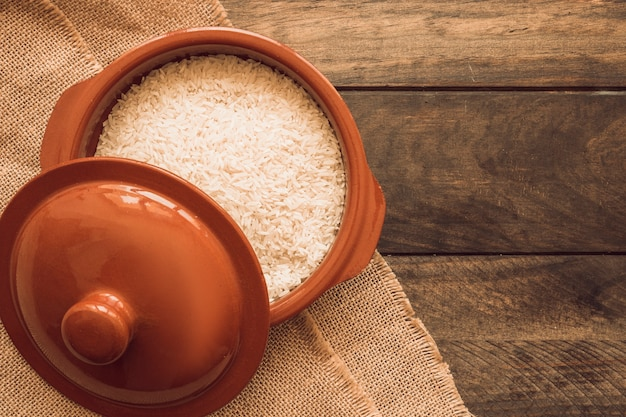 A open rice grains bowls with lid on wooden table Free Photo