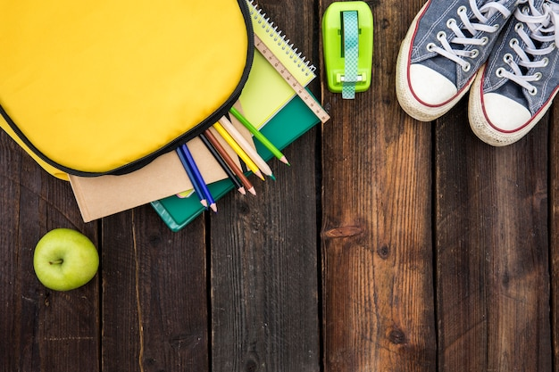 Open schoolbag with stationery and gumshoes Free Photo