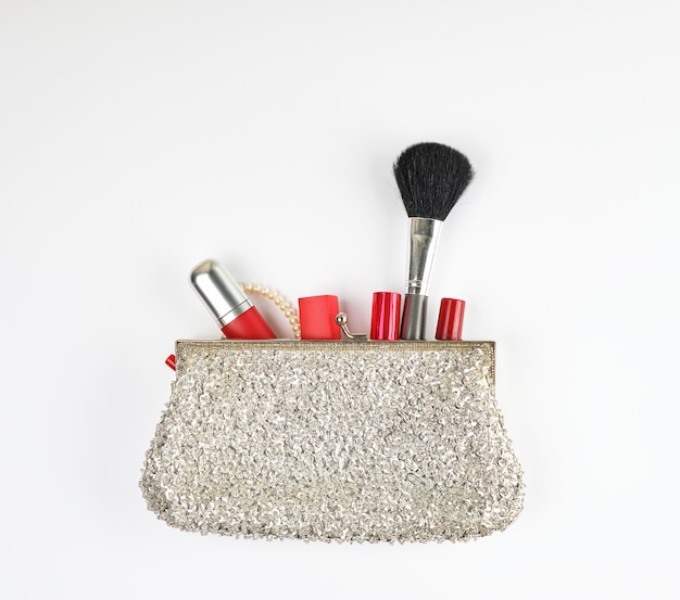 Open silver clutch and cosmetics fell out of the middle Premium Photo