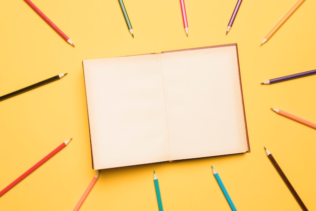 Open sketchbook surrounded by pencils of different colors Free Photo