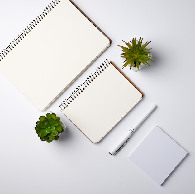 Open spiral notebook with empty sheets and pots with green indoor plants Premium Photo