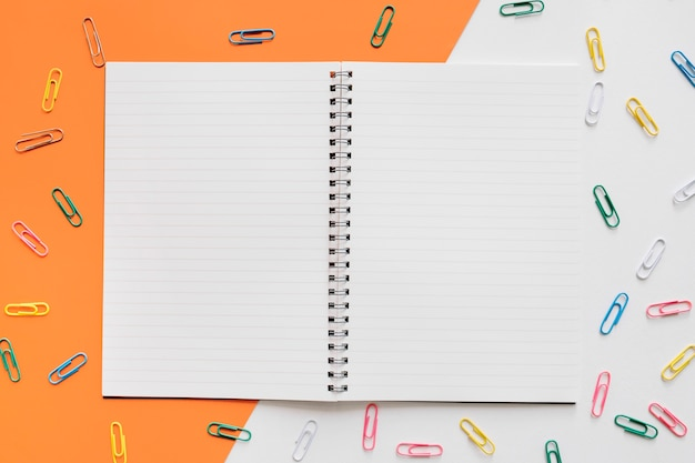 Open spiral notepad surrounded by various colorful push pins on colorful background Free Photo