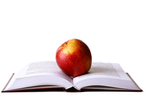 Open student book with red apple Free Photo
