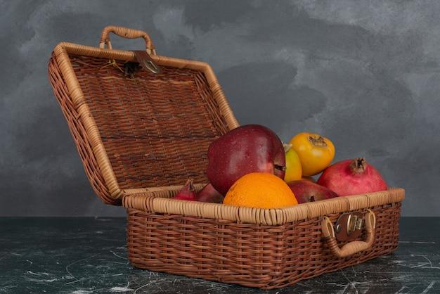 大理石の壁に果物でいっぱいのスーツケースを開きます。 無料写真