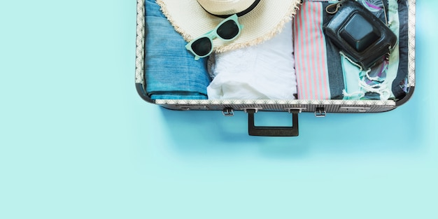 Open suitcase with female clothes for trip on pastel blue. Premium Photo