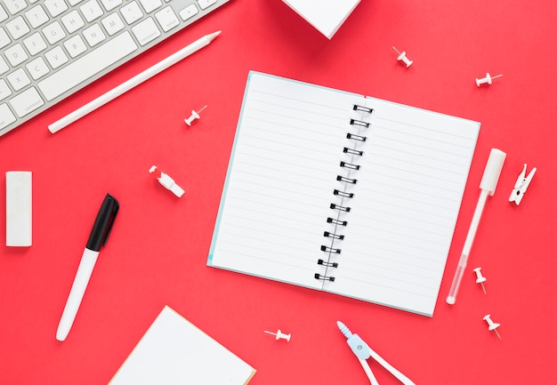 Opened blank notebook and stationery on red surface Free Photo