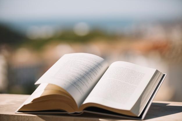Opened book on ledge Free Photo