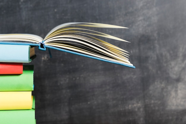 Opened book on vivid pile against chalkboard Free Photo