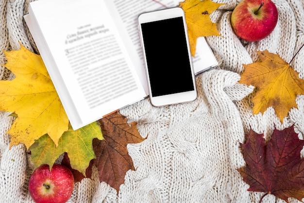 Открыла книгу с телефоном и яблоком рядом Premium Фотографии