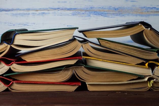 Открытые книги сложены друг на друга на белой деревянной стене Premium Фотографии