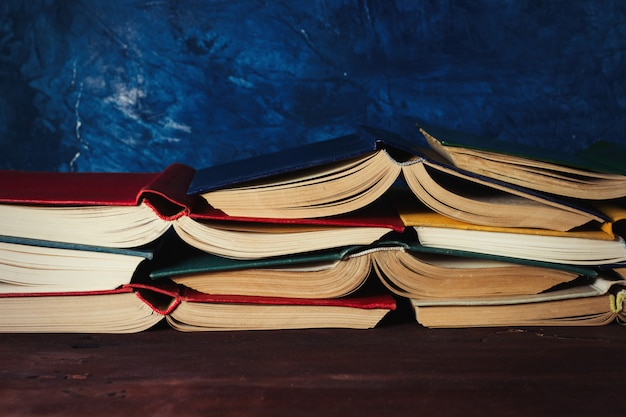 Открытые книги, сложенные друг на друга на деревянном столе и темно-синей стене Premium Фотографии