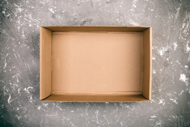 Opened brown blank cardboard box on cement gray surface Premium Photo