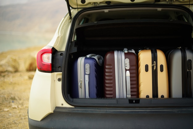 Opened car trunk full of suitcases, luggage, baggage. Premium Photo