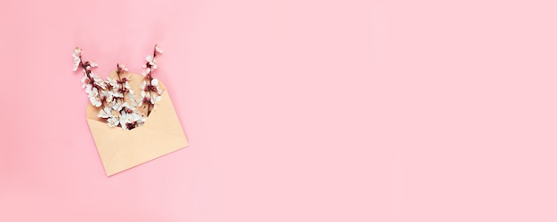 Opened craft paper envelope full of spring blossom flowers on pink background. Premium Photo