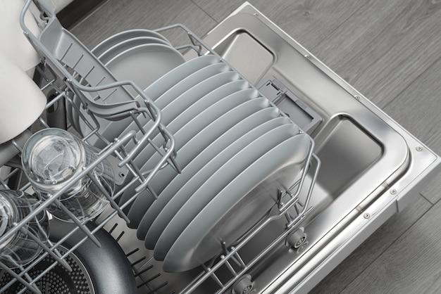 Opened domestic dishwasher with cleaned dishware Premium Photo