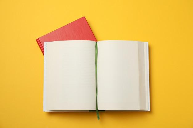Раскрытая пустая книга и красная книга на желтом космосе, месте для текста Premium Фотографии