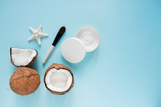 Opened glass jar with fresh coconut oil and ripe coconuts on blue Premium Photo