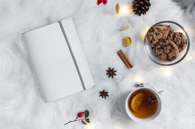 Opened notebook on plaid near tea with cookies Free Photo