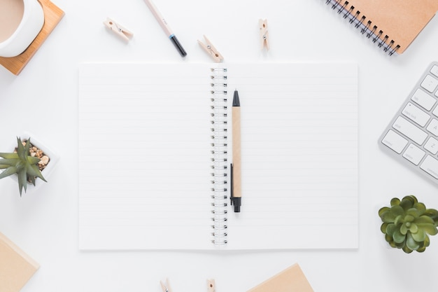 Opened notebook with pen near stationery Free Photo