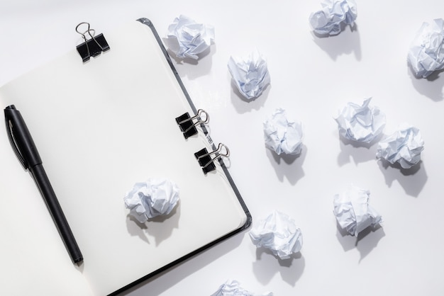 Opened notepad on a white background with crumpled papers Premium Photo