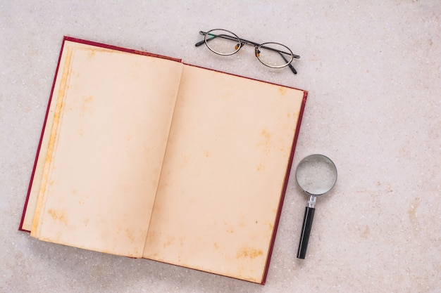 Opened old book, magnifying glass and eye glasses on white marble table, top view Premium Photo