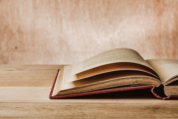 Opened old book on wooden table Premium Photo