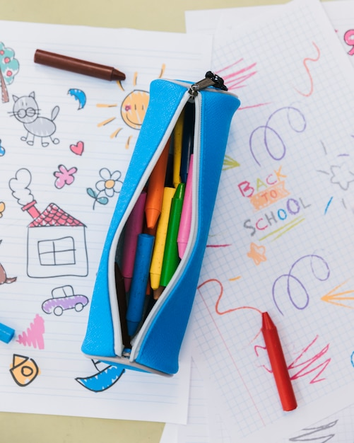 Opened pencil case with wax crayons placed on kid drawings Free Photo