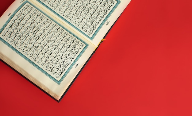 Opened quran on a plain burgundy space Premium Photo