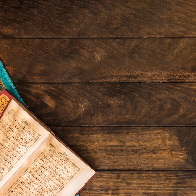 Opened quran on timber tabletop Free Photo
