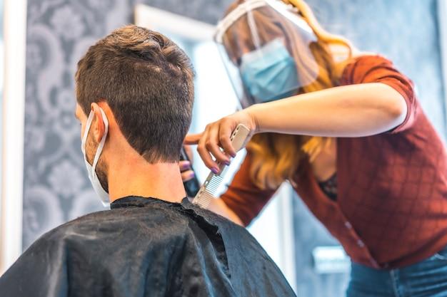コロナウイルスの流行後の美容院のオープン、covid-19。セキュリティ対策、フェイスマスク、防護スクリーン、社会的距離。金髪白人美容院 Premium写真
