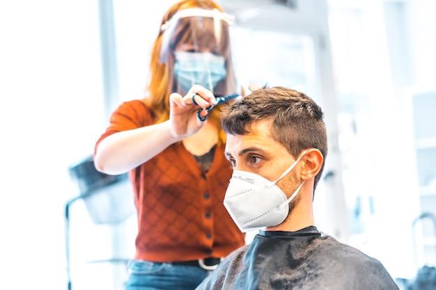 コロナウイルスの流行後の美容院のオープン、covid-19。セキュリティ対策、フェイスマスク、防護スクリーン、社会的距離。クライアントの少年にハサミで髪を切る美容師 Premium写真