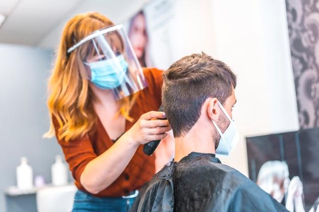 コロナウイルスの流行後の美容院のオープン、covid-19。セキュリティ対策、フェイスマスク、防護スクリーン、社会的距離。新しい通常に取り組んでいる美容師 Premium写真
