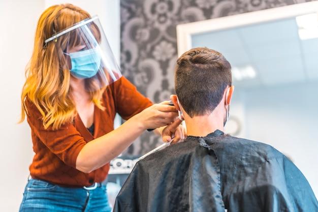 コロナウイルスの流行後の美容院のオープン、covid-19。セキュリティ対策、フェイスマスク、防護スクリーン、社会的距離。若いブルネットを扱う美容師 Premium写真