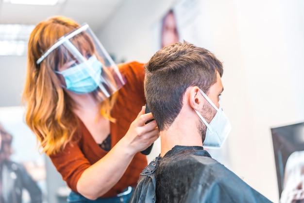コロナウイルスの流行後の美容院のオープン、covid-19。セキュリティ対策、フェイスマスク、防護スクリーン、社会的距離。新しい通常の髪を切る美容師 Premium写真