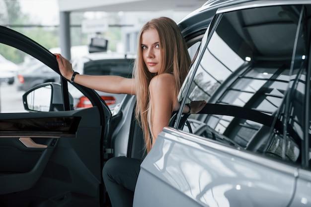 Открываю дверь. девушка и современная машина в салоне. днем в помещении. покупка нового автомобиля Бесплатные Фотографии