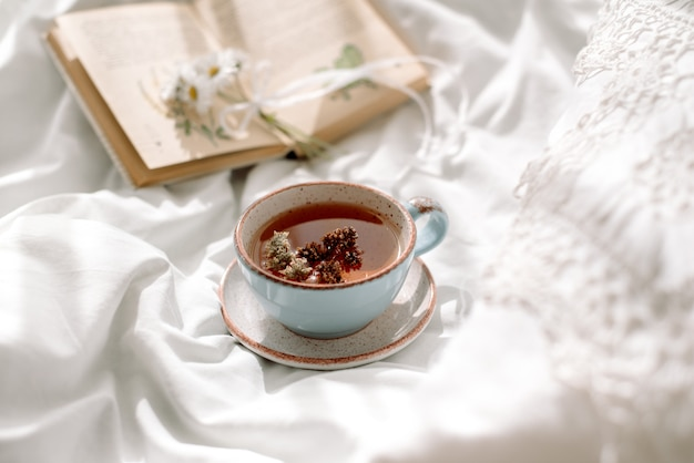 透かしレース、綿の白い毛布。本の植物学、ミント、夏のデイジーの花から作られた天然ハーブティーのマグカップ。ベッドで朝の朝食。プロヴァンスとレトロなスタイル。すっきりとした心地よさとさわやかさ。 Premium写真