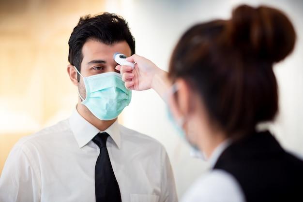 オペレーターが情報カウンターでデジタルサーモミッターの訪問者による発熱を確認し、コロナウイルス(covid-19)からスキャンして保護する Premium写真