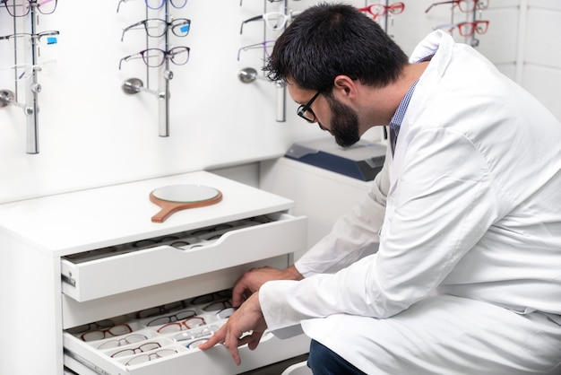 Ophthalmologist choosing glasses from a drawer in the optical store Premium Photo