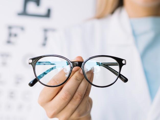 Ophthalmologist doctor holding pair of eyeglasses Premium Photo